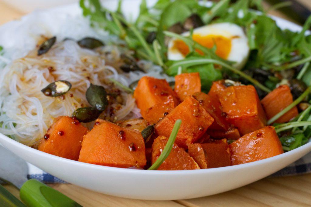 Sałatka ze słodkich ziemniaków z makaronem Vermicelli, jajkiem, rukolą, pestkami dyni i sosem daktylowym.