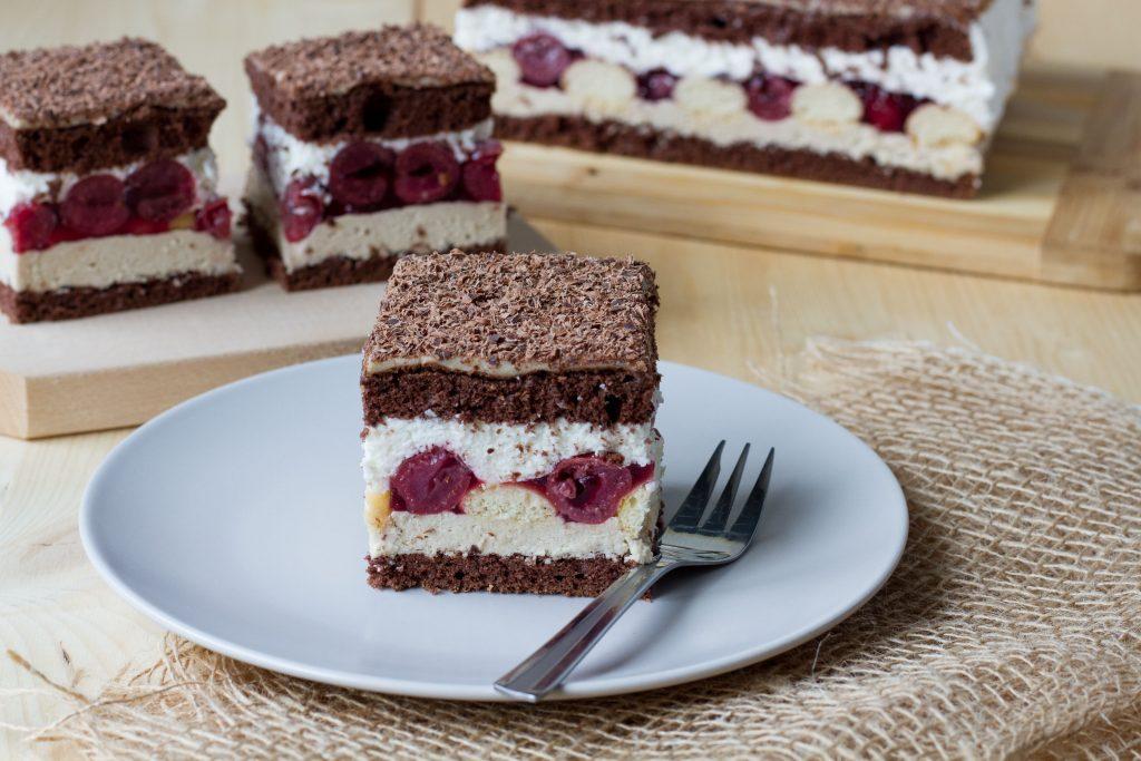Ciasto kakaowe przełożone masą chałwową, biszkoptami, wiśniami i bitą śmietaną.